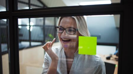 Happy and confident girl Manager plans to work on the project. young business woman wearing glasses inside a bright office with a glass partition glues colored leaves for effective project management. 스톡 콘텐츠
