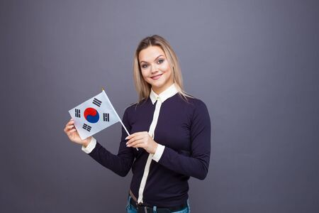 Immigration and the study of foreign languages, concept. A young smiling woman with a Republic of Korea flag in her hand. Girl waving a Republic of Korea flag on a gray background