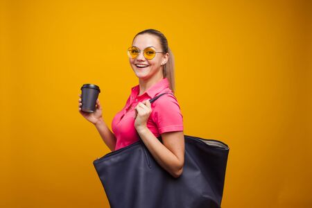 Business positive girl in casual style hurries on business and drinks coffee to take away. Coffee break, cute blonde in sunglasses and t-shirt with bag on shoulder, portrait on yellow background Reklamní fotografie