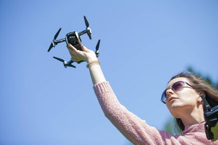 A young woman in a clearing in a park launches, checks, holds the drone with her outstretched arm above her head, in another control panel. Outdor. Copyspace. The woman is partially visible. Stock fotó