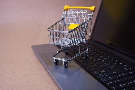 E-Commerce, concept. Online shopping, shopping cart on laptop keyboard. Shopping in online stores and online payments. Empty shopping cart on computer keyboard