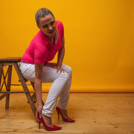 young woman suffers from uncomfortable high-heeled shoes, portrait in the Studio on a yellow background. girl takes off her stiletto Shoe and experiences pain from corns