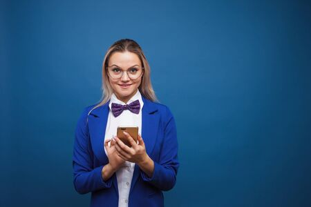 Cute and funny businesswoman in a stylish blue jacket and bow tie uses a smartphone. Girl in suit with mobile phone communicates in chat messenger
