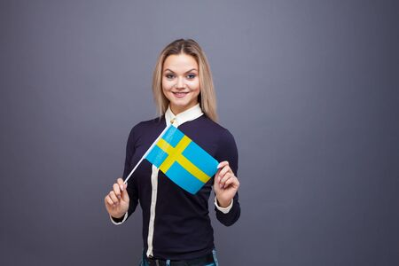 Immigration and the study of foreign languages, concept. A young smiling woman with a Sweden flag in her hand. Girl waving a Swedish flag on a gray background Stock fotó