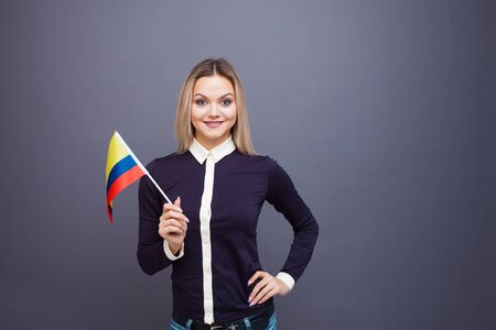 Immigration and the study of foreign languages, concept. A young smiling woman with a Colombia flag in her hand. Girl waving a Colombia flag on a gray background
