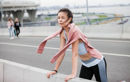 Fitness sport girl resting after intensive evening run, young attractive runner taking break after jogging outdoors, female jogger in bright sportswear smiling looking away, advertising for sports.