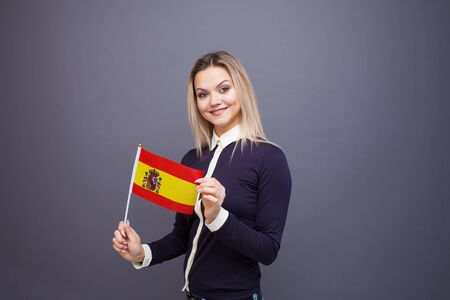 Immigration and the study of foreign languages, concept. A young smiling woman with a Spain flag in her hand. Girl waving a Spanish flag on a gray background