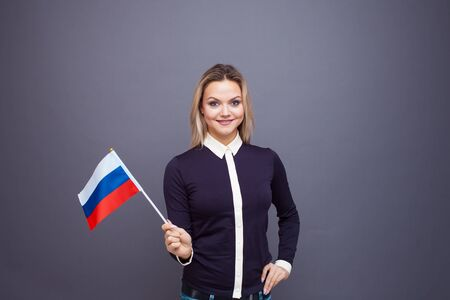 Immigration and the study of foreign languages, concept. A young smiling woman with a Russia flag in her hand. Girl waving a Russia flag on a gray background