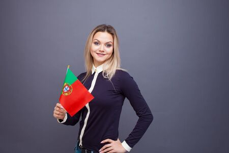Immigration and the study of foreign languages, concept. A young smiling woman with a Portugal flag in her hand. Girl waving a Portuguese flag on a gray background Banco de Imagens