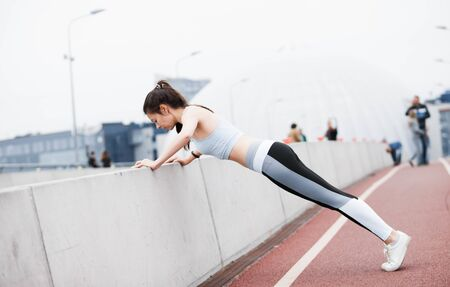 A young sports woman in a fitness suit is pushing up from the curb, parapet of the bridge, against the backdrop of an urban cityscape. Copyspace.