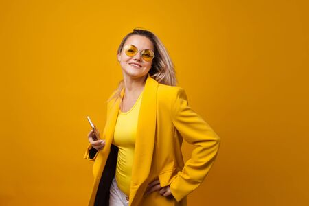 Stylish positive young woman on yellow background uses a smartphone, copy space. Social networks and communication apps. Studio portrait of a Girl in yellow jacket and yellow sunglasses, one tone look