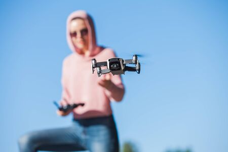 Standing with a bended knee, a young woman in pink hoodie and dark glasses controls the drone's outdoor flight control panel in nature. Full-length photo. Blurred background. Drone in the foreground. Imagens