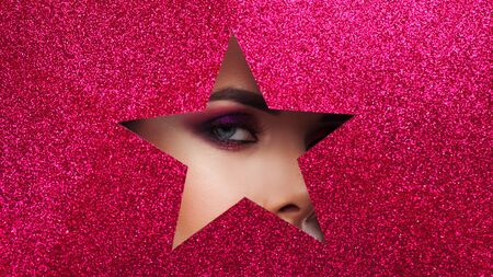 Bright glamorous makeup, in a hole in the shape of a shining star. Female eye Peeps in the hole, eye makeup, luxury lashes
