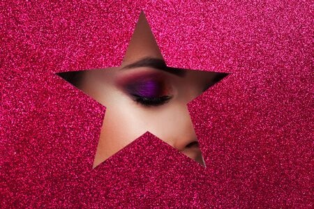 You are a superstar, bright evening makeup, a fragment of a beautiful young womans face in a cutout in the shape of a star. Shining scarlet background Banco de Imagens