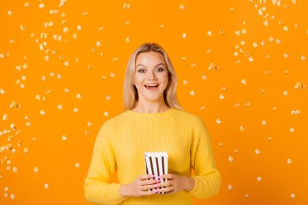 Fan of movies and TV series. Girl in yellow sweater and popcorn on yellow background