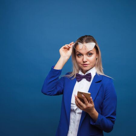 Cute and funny businesswoman in a stylish blue jacket and bow tie uses a smartphone. Mobile applications for business and life, concept copy space