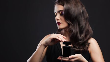 Attractive young brunette woman and a bottle with a new fragrance, use perfume. Portrait on a black background