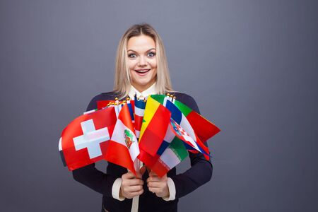Cheerful young woman with a large set of flags of different countries of the world. polyglot, and learning foreign languages