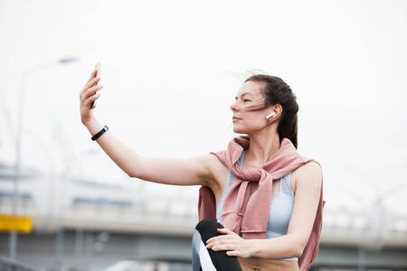 Athletic young woman in a sports uniform checks a smartphone, installs music, checks the fitness application on a smartphone, catches a network, sitting on the curb.