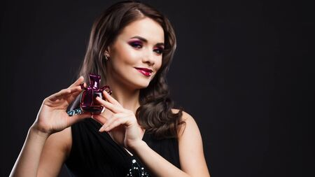 beautiful young woman with bright makeup is holding a bottle of perfume. Gorgeous young brunette in a chic evening look.