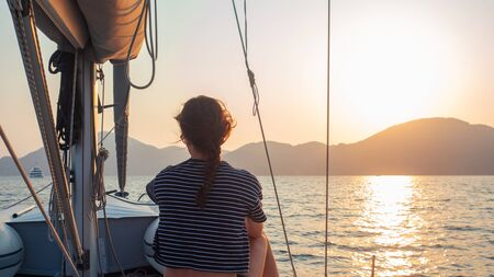 attractive young woman in a striped t-shirt enjoys the sunset on the deck of a sailing yacht. Sailor girl looks into the distance. Sailing regatta, sea voyage
