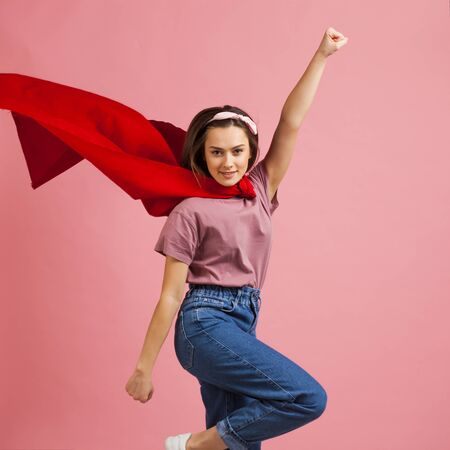 Superpowers, a supergirl in a red Cape is flying to the rescue. Cute young girl superhero