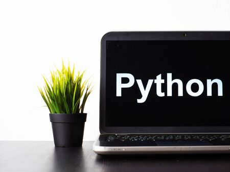Python programming language. Programming training, the concept of computer courses. Laptop on the table with Python written on the screen