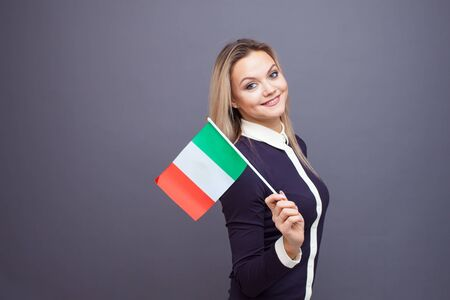 Immigration and the study of foreign languages, concept. A young smiling woman with a Italy flag in her hand. Girl waving a Italian flag on a gray background