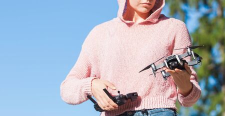 A young woman in a pink hoodie and dark glasses holds, launches, catches the drone with one hand, and holds the control panel in the other. The woman is partially visible. Outdor. Copyspace.
