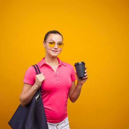 Cute blonde in sunglasses and t-shirt with bag on shoulder, drinking her hot drink, portrait on yellow background copy space