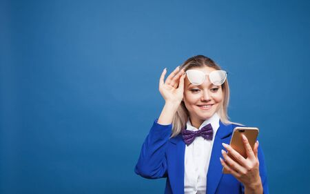 Cute and funny businesswoman in a stylish blue jacket and bow tie uses a smartphone. Girl in suit with mobile phone happily laughs, copy space