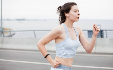 Fitness sport girl on intensive evening run, young attractive runner jogging outdoors, female jogger in bright sportswear smiling looking away, advertising for sports. Banco de Imagens