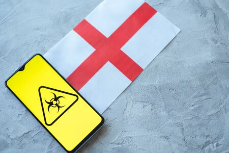 Epidemiological situation in the country England. Flag and smartphone with news and a biohazard symbol. The pandemic virus, concept