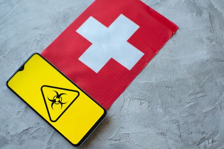 Epidemiological situation in the country Switzerland. Flag and smartphone with news and a biohazard symbol. The pandemic virus, concept
