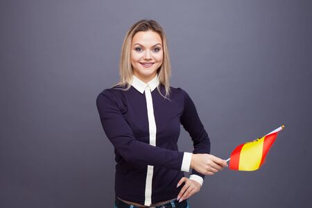 Immigration and the study of foreign languages, concept. A young smiling woman with a Spain flag in her hand. Girl waving a Spanish flag on a gray background Archivio Fotografico