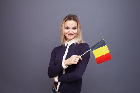 Immigration and the study of foreign languages, concept. A young smiling woman with a Belgium flag in her hand. Girl waving a Belgian flag on a gray background