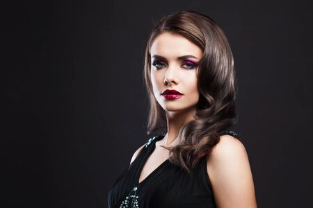 Portrait of a young luxurious woman in a low key. Bright makeup with scarlet lipstick, hairstyle with curls, portrait on a black background