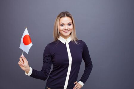 Immigration and the study of foreign languages, concept. A young smiling woman with a Japan flag in her hand. Girl waving a Japanese flag on a gray background