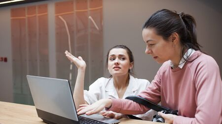 Coaching and mentoring, a professional helps a Junior colleague. The internship concept. Two young women look at one laptop and discuss the topic