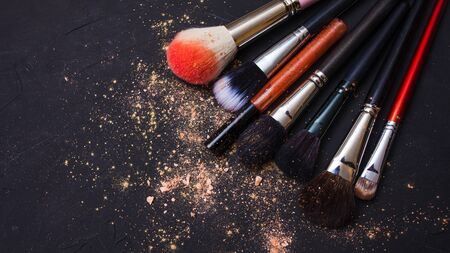 Set of different makeup brushes, makeup tools, textured dark background. Powder and eye shadow, copy space and Shine