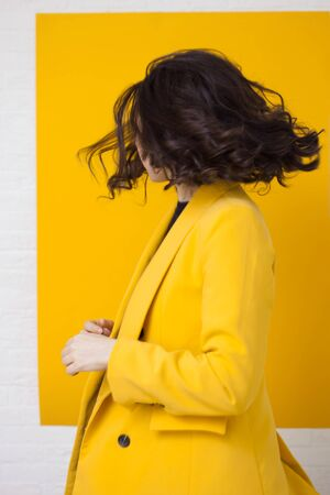 Stylish young woman in a yellow jacket on a yellow background, happy and dancing. Background with white frame
