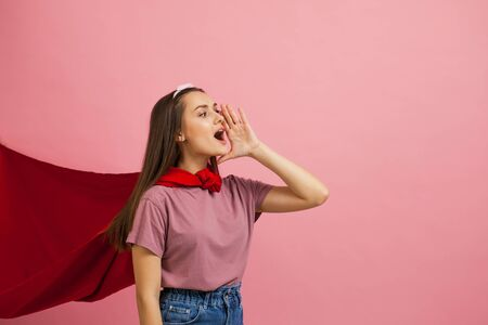 Superheroine, a young female superhero in a red Cape shouts loudly