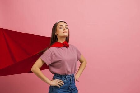 Superheroine, a young female superhero in a red Cape. Everyone can become a hero, a cute young girl in a red raincoat of a comic book superhero in jeans and a t-shirt