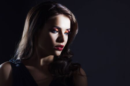 luxurious and mysterious beauty in Noir style, a portrait on a black background, deep shadows and a mysterious look. Fatal lady close-up Stock Photo
