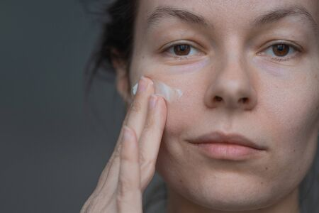 Skin care, portrait of a young beautiful woman close-up, without makeup and retouching. health of the skin and face care, concept. Trending portrait showing real skin, young woman using face cream