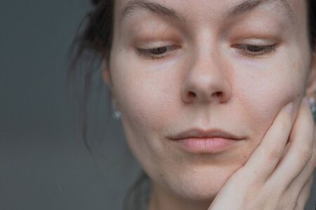 Skin care, portrait of a young beautiful woman close-up, without makeup and retouching. health of the skin and face care, concept. Trending portrait showing real skin, young woman using face cream Archivio Fotografico