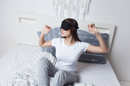 Young woman woke up in the morning in bed wearing a sleep mask, good morning, Wake up and sleep mode