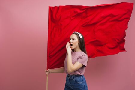 activist and revolutionary, young woman with a red flag on a pink background. Feminism and the struggle for rights, concept 版權商用圖片
