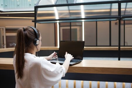 Lifestyle portrait in the interior. A young woman with headphones works at a laptop and participates in an online meeting, remote work and freelancing, modern communications. 写真素材