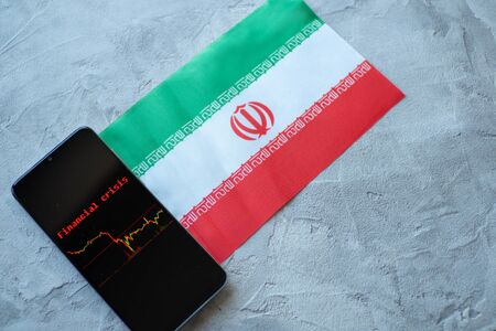 The economic crisis, the news and the schedule drop-down on the smartphone screen. The financial crisis in Iran. Flag